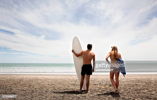 Young couple standing on beach holding surfboard and boogie board