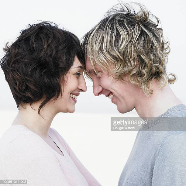 Young couple standing on beach, smiling, close-up