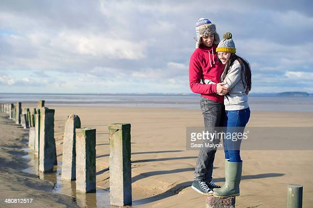 Young couple standing on groynes, Brean Sands, Somerset, England