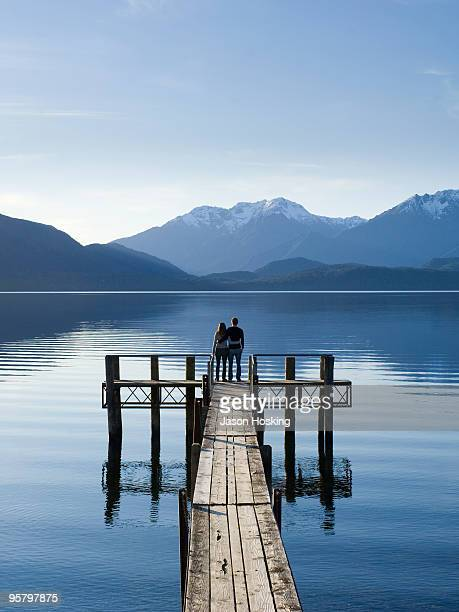 Young couple standing on lake jetty