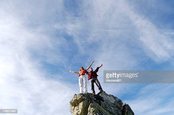 Young couple standing on mountain peak, arms out, low angle view