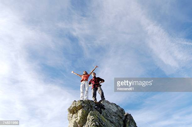 Young couple standing on mountain peak, low angle view
