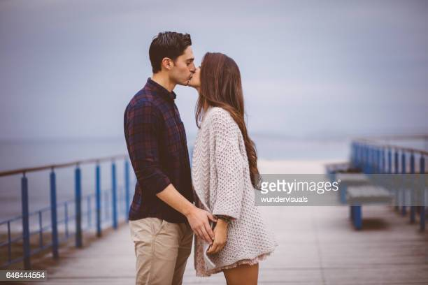young couple standing on pier and kissing. - kissing stock pictures, royalty-free photos & images