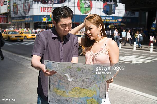 Young couple standing on street corner holding map, New York City