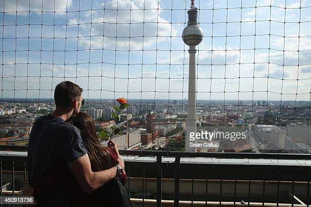 A young couple standing on the rooftop terrace of a hotel look out at the broadcast tower at Alexanderplatz on June 18 2014 in Berlin Germany...