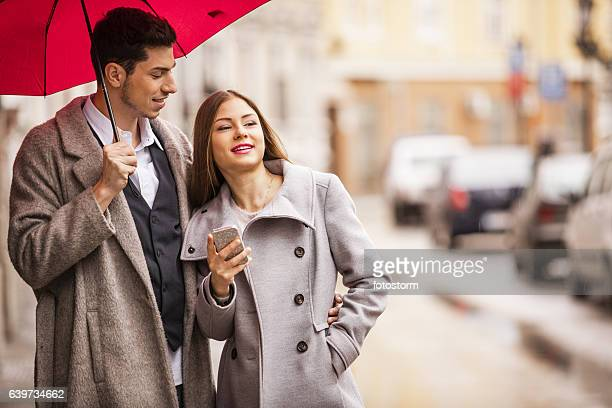 Young couple standing on the street with mobile device
