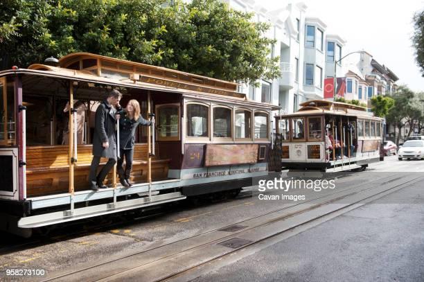 young couple standing on tramway at street - zona de la bahía de san francisco fotografías e imágenes de stock