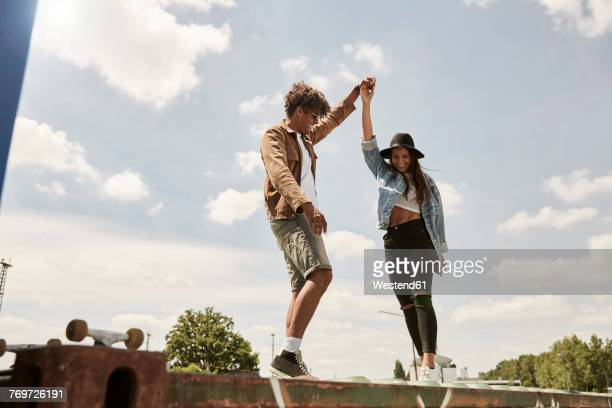 Young couple standing on wall, raising arms