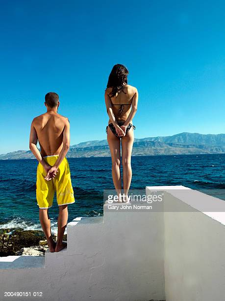 Young couple standing on white steps by sea, rear view