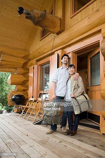 Junges Paar stehen außerhalb log cabin