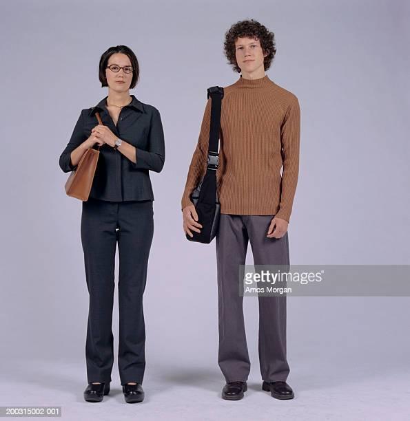 young couple standing side by side, posing in studio, portrait - côte à côte photos et images de collection