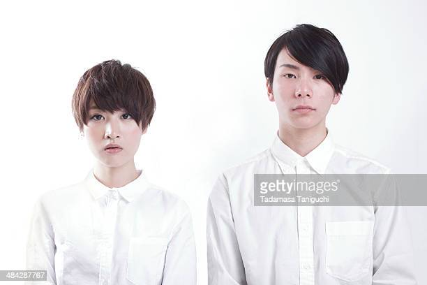 young couple standing to look straightforward - 20代 ストックフォトと画像
