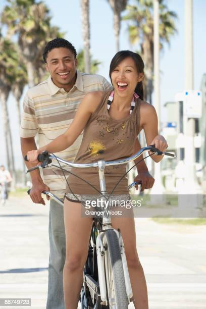 Young couple standing with tandem bicycle