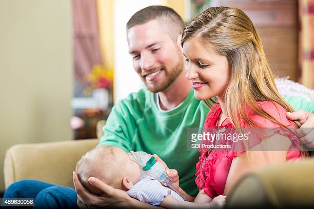 young couple staring at newborn daughter together - cystic fibrosis stock photos and pictures