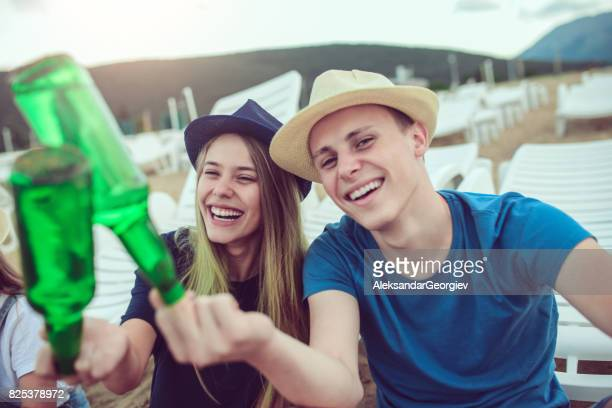 young couple sticking fingers in beer bottle at the beach - freaky couples imagens e fotografias de stock