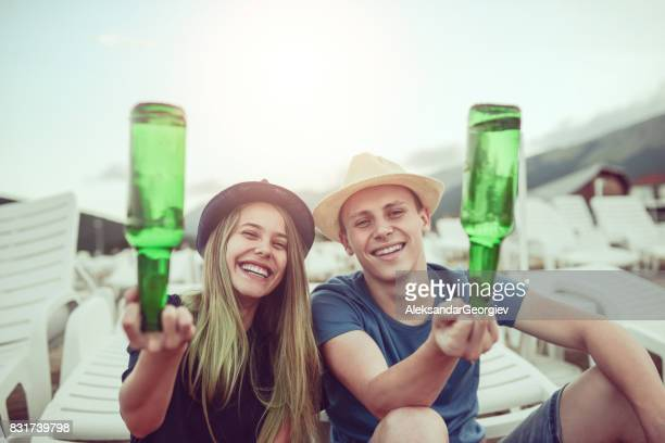 young couple sticking fingers in beer bottle at the beach - middle finger funny stock photos and pictures