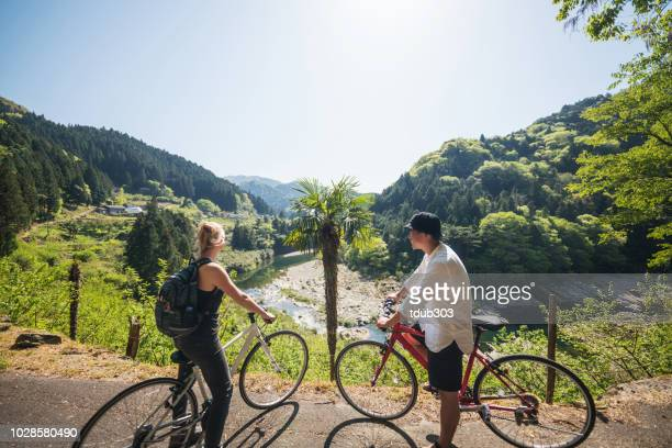 Young couple stop to enjoy the view cycling in the mountains