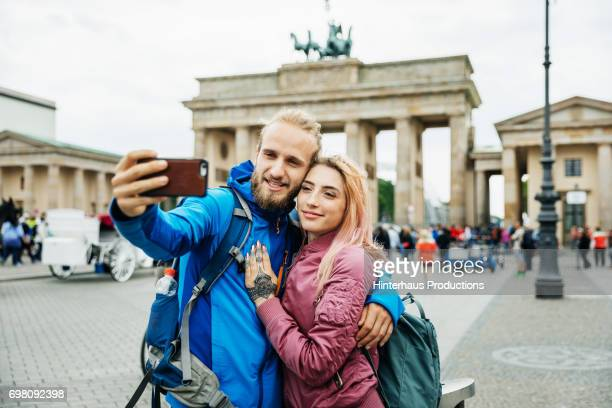 Young Couple Stop To Take Selfie In front Of Brandenburg Gate in Berlin