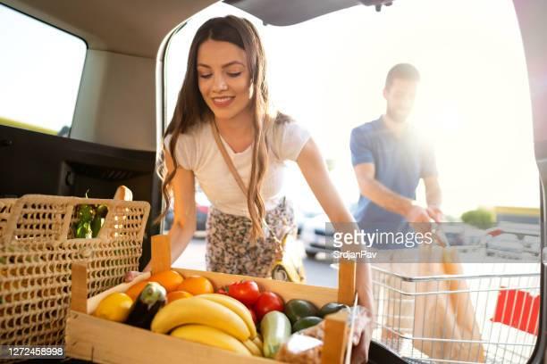 jeunes couples stockant l'épicerie du supermarché dans un coffre de voiture - fruit exotique photos et images de collection