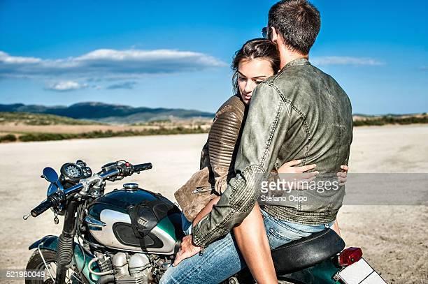 Young couple straddling motorcycle on arid plain, Cagliari, Sardinia, Italy