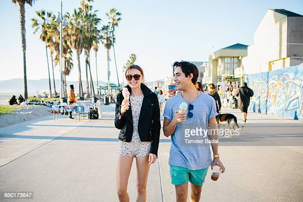 young couple strolling eating ice cream cones, venice beach, california, usa - city of los angeles stock pictures, royalty-free photos & images