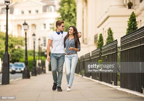 young couple strolling on city street, london, uk - casal heterossexual - fotografias e filmes do acervo