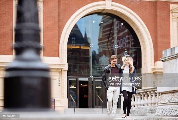 Young couple strolling outside Albert Hall, London, England, UK