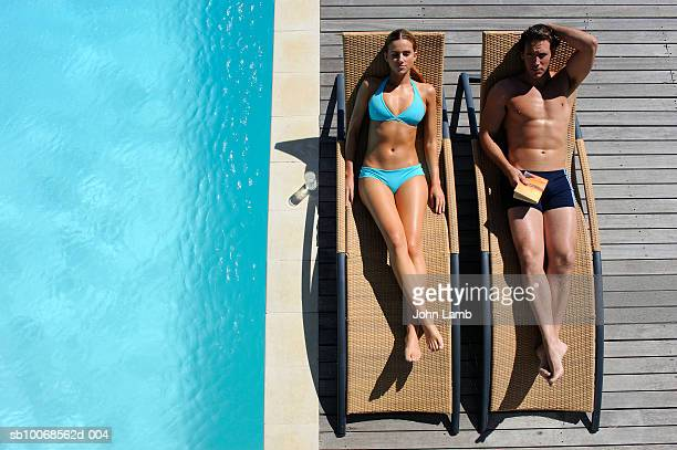 Young couple sunbathing at poolside, view from above