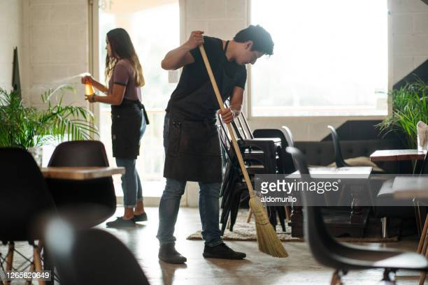 young couple sweeping and cleaning coffee shop - sweeping stock pictures, royalty-free photos & images