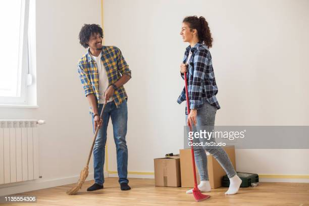 young couple sweeping - broom sweeping stock pictures, royalty-free photos & images