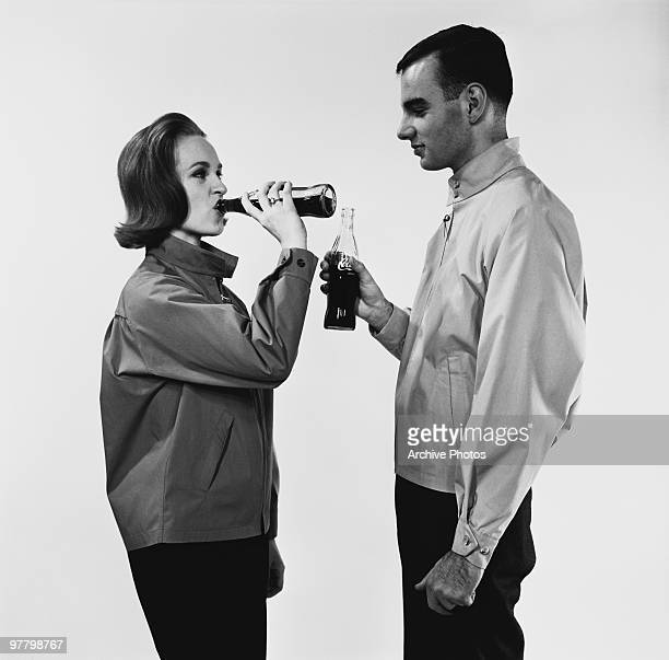 A young couple swigging CocaCola from bottles circa 1960