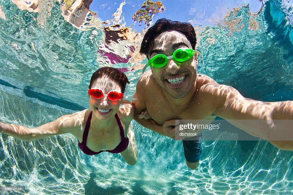 Young couple swimming underwater in pool : Stock Photo