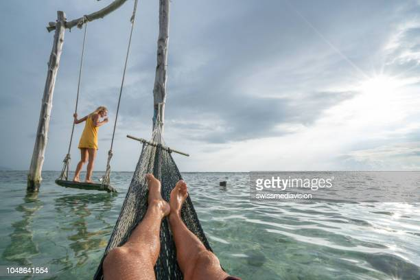 young couple swinging on the beach by the sea, beautiful and idyllic landscape. people travel romance vacations concept. personal perspective of man on sea hammock and girlfriend on sea swing. - gili trawangan stock photos and pictures