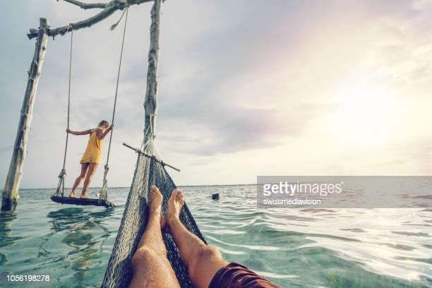 young couple swinging on the beach by the sea, beautiful and idyllic landscape. people travel romance vacations concept. personal perspective of man on sea hammock and girlfriend on sea swing. - indonesia stock pictures, royalty-free photos & images