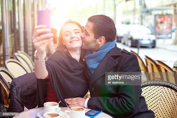 Young couple take selfie in a Paris bistro.