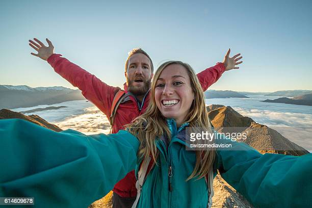 Young couple take selfie on mountain summit