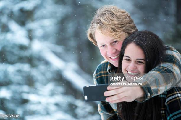 Young couple take selfie portrait, snowy setting