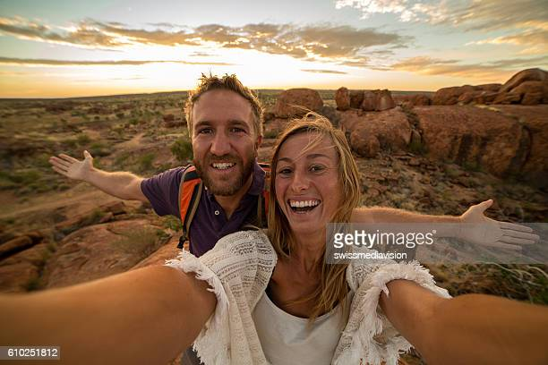 Young couple take selfie portrait with spectacular landscape at sunrise