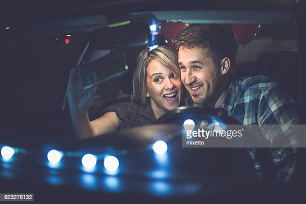 Young couple take the self portrait in the car