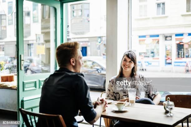 young couple taking a break together for drink in cafe - atividade romântica - fotografias e filmes do acervo