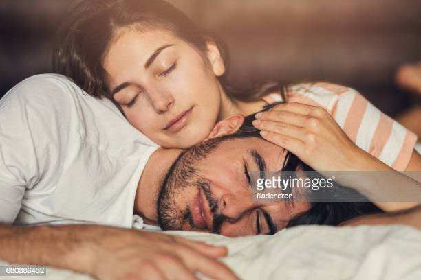 young couple taking a nap - romantic young couple sleeping in bed stock photos and pictures