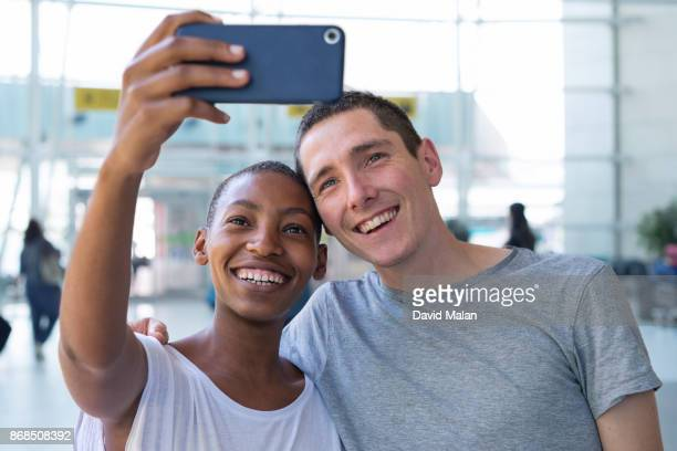 young couple taking a selfie at an airport.