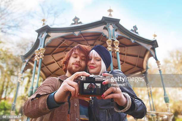 Young couple taking a selfie in front of pavilion