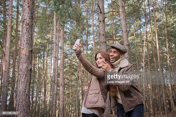 A young couple taking a selfie on a forest walk in Autumn