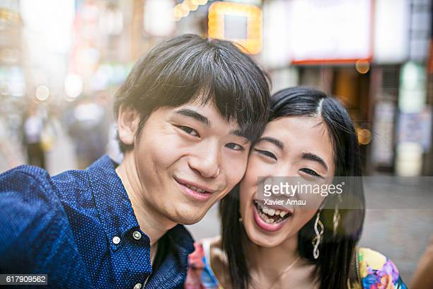 Young couple taking a selfie on city street