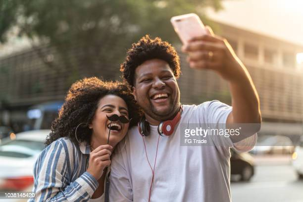 young couple taking a selfie outdoors - prop stock photos and pictures
