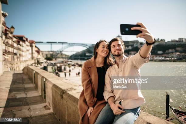 casal jovem tirando uma foto de selfie com um smartphone moderno - portugal - fotografias e filmes do acervo
