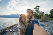 young couple taking selfie portrait lake