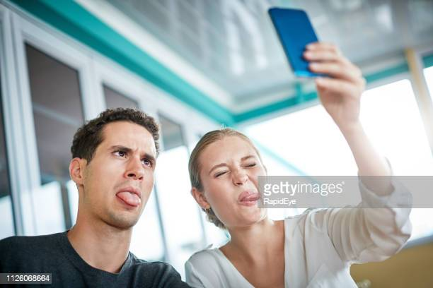 Young couple taking a selfie  pull funny faces playfully