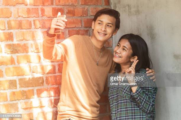 Young couple taking a selfie using smart phone outdoor